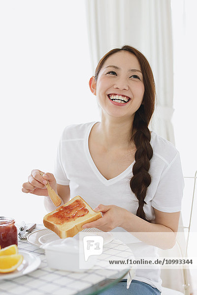 Young attractive Japanese woman having breakfast at home