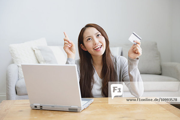 Young attractive Japanese woman doing online shopping at home