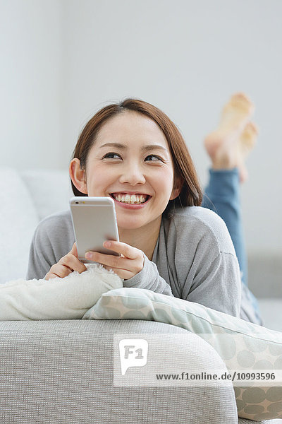 Young attractive Japanese woman with smartphone on the sofa