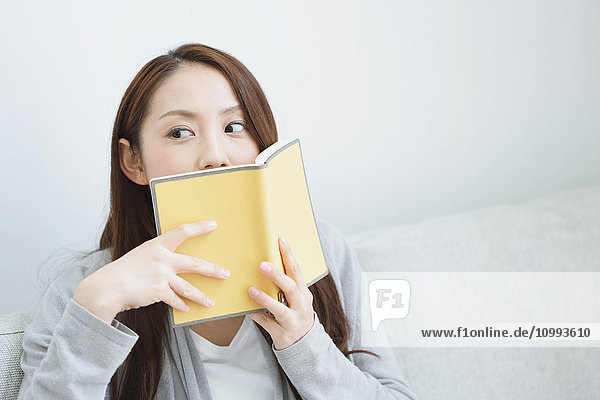 Young attractive Japanese woman with book on the sofa