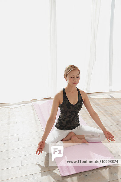 Attractive young Japanese practicing yoga in an airy room