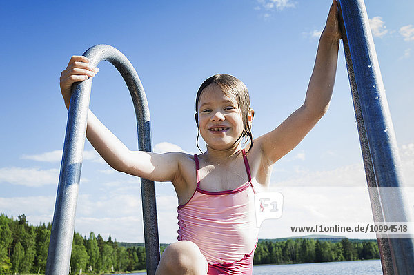 Young girl in swim suit climbing ladder out of lake  Sweden