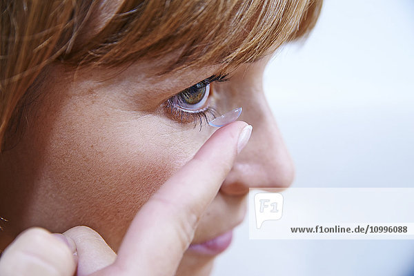 Woman inserting a contact lens.