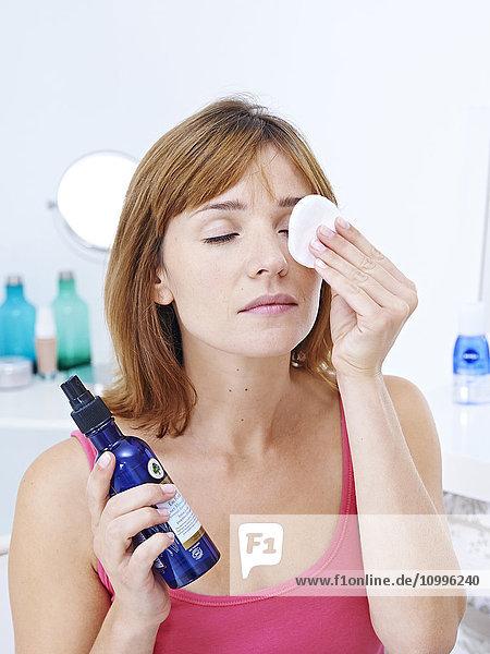Woman applying cornflower floral water on her eyes.