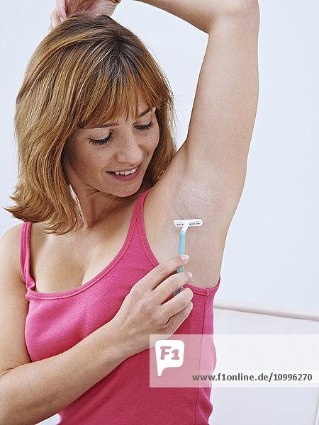 Woman shaving her armpits.