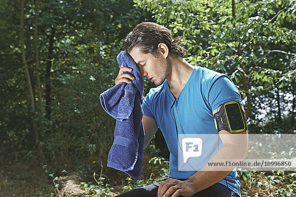 Man wiping his face after exercising.