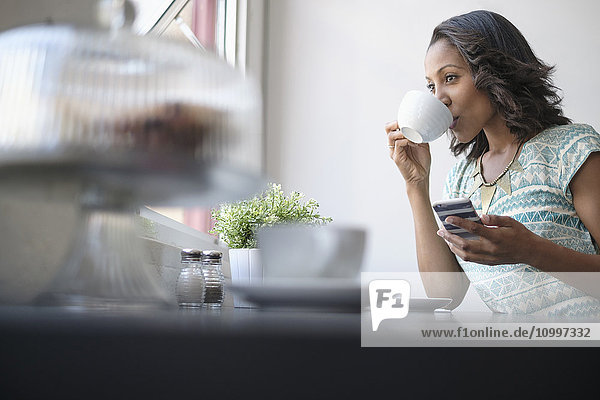 Woman drinking coffee and using phone