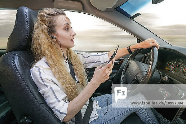 Woman using mobile phone during driving car