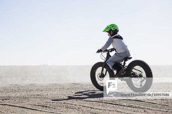 Boy (6-7) riding bicycle