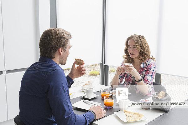 Mid-adult couple eating breakfast