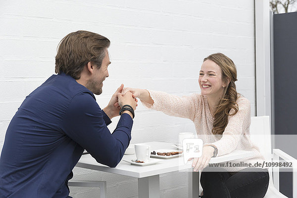 Man holding woman's hand as they seat at table with coffee