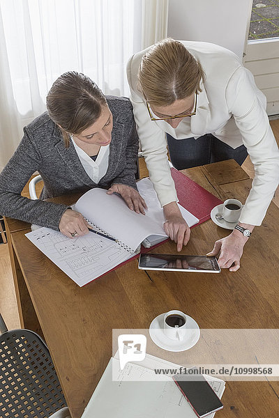 Businesswomen working with tablet and documents