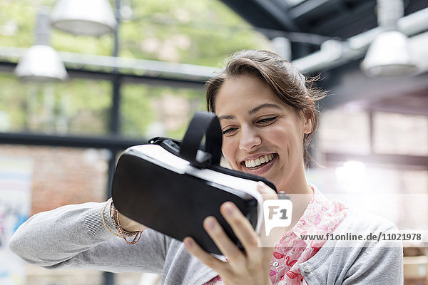 Smiling woman trying virtual reality simulator glasses at technology conference