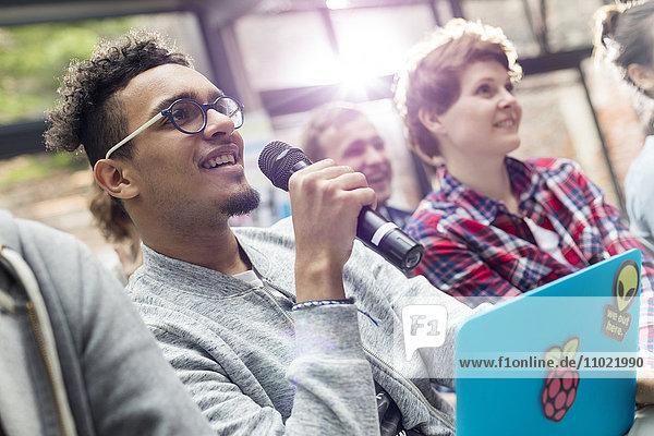 Mann im Publikum mit Laptop stellt Frage mit Mikrofon bei der Konferenz