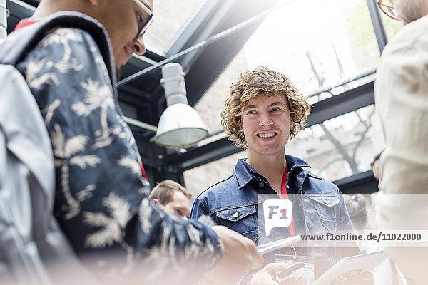 Lächelnder Mann mit digitalem Tablett auf der Technologiekonferenz
