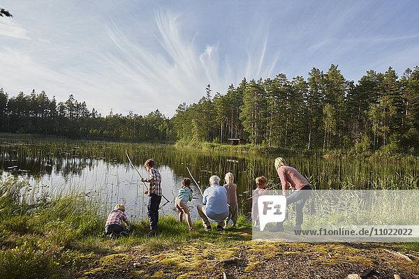 Großeltern und Enkelkinder beim Angeln am sonnigen Seeufer im Wald