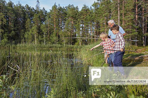 Großvater unterrichtet Enkel beim Fischen am sonnigen Seeufer