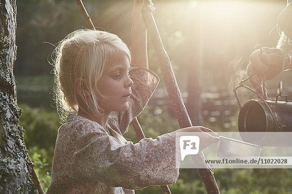 Mädchen erhält heiße Suppe in sonnigen Wäldern