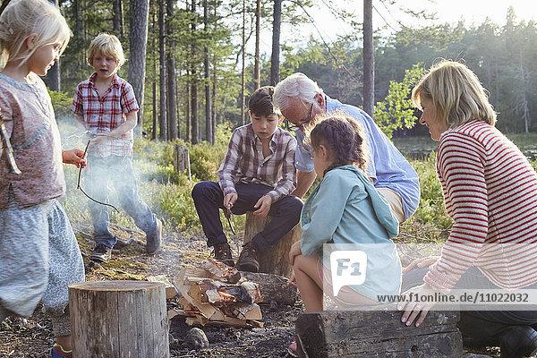 Großeltern und Enkelkinder beim Lagerfeuer am Seeufer