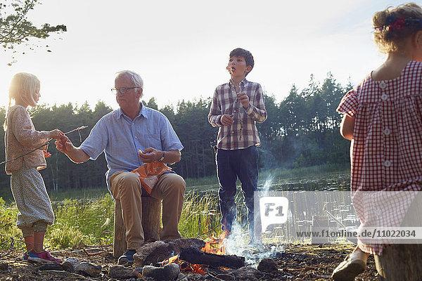 Großvater und Enkel am Lagerfeuer am Seeufer