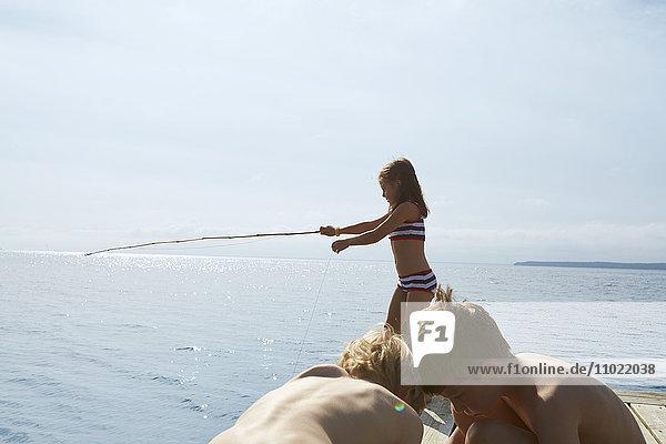 Mädchen im Bikini fischen vor dem sonnigen Dock