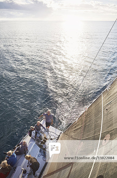 Freunde segeln auf einem Segelboot auf dem sonnigen Ozean