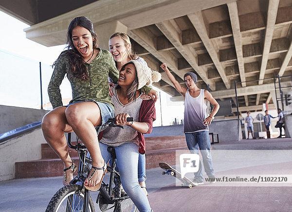 Verspielte Teenager-Freunde beim BMX-Radfahren und Skateboarden im Skatepark