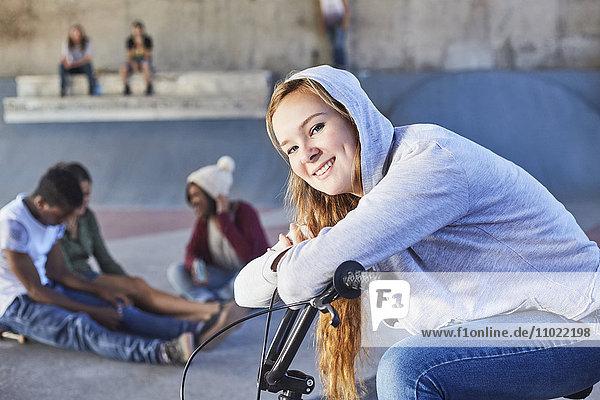 Portrait lächelndes Teenagermädchen auf BMX-Fahrrad im Skatepark