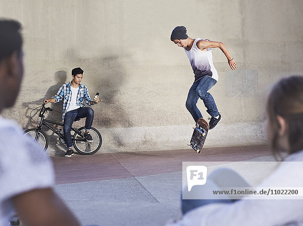 Freunde sehen dem Teenager beim Skateboardfahren im Skatepark zu.