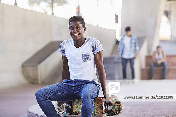 Porträt lächelnder Teenager auf dem Skateboard im Skatepark