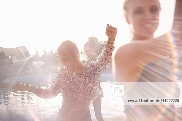 Junge Frau tanzt auf sonniger Poolparty