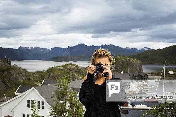 Woman photographing through digital camera against mountains Woman photographing through digital camera against mountains