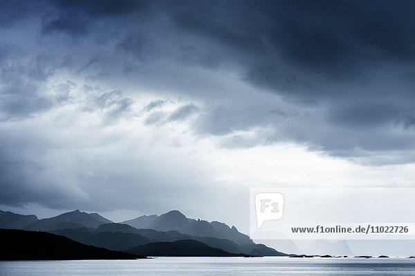 Silhouette mountain range by lake against cloudy sky