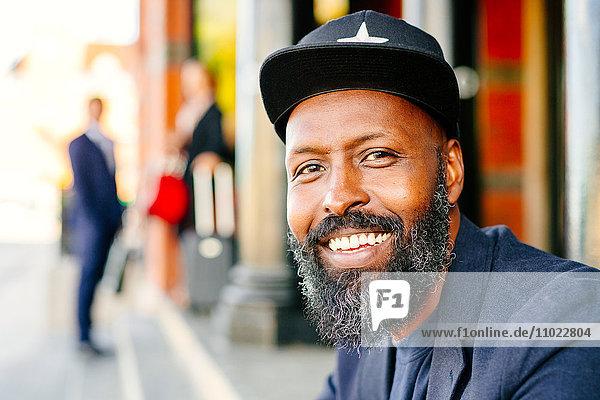 Portrait of happy businessman sitting outside railroad station