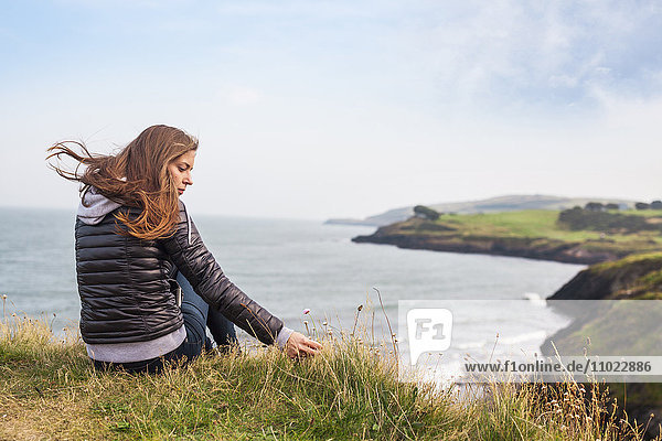 Rear view of woman sitting on hill by sea against sky Rear view of woman sitting on hill by sea against sky
