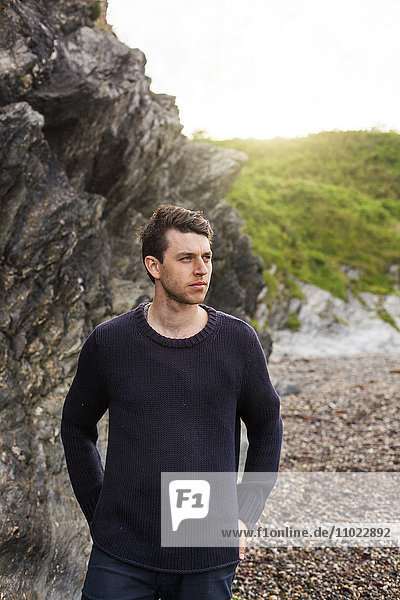 Thoughtful young man looking away while standing at beach