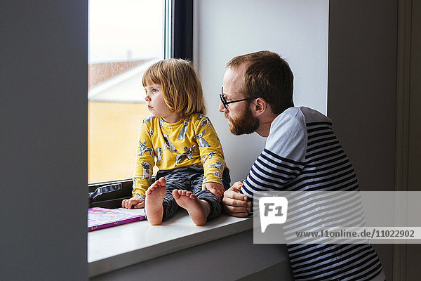 Mid adult man with daughter looking through window at home