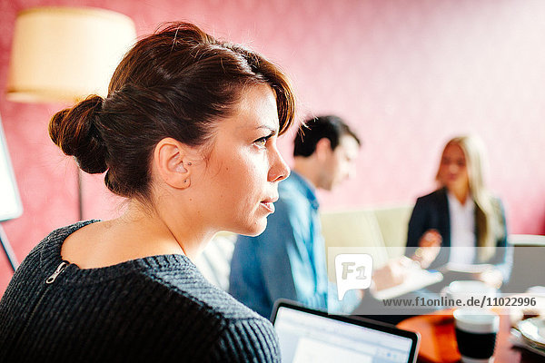 Rear view of businesswoman looking away during meeting in office