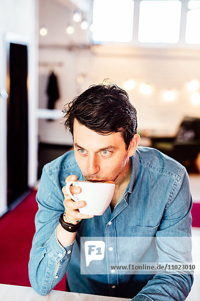 Thoughtful businessman drinking coffee in office