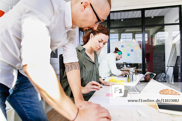 Mid adult businesswoman with colleagues working at table in creative office