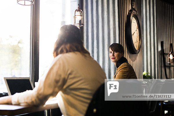 Woman looking at friend while sitting at cafe