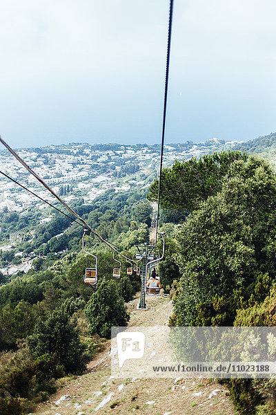 High angle view of young man in ski lift over mountain against sky