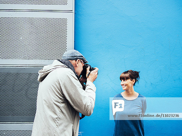 Man photographing woman standing against blue wall
