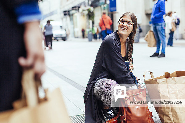 Happy woman looking at female friend while searching something in bag at city street