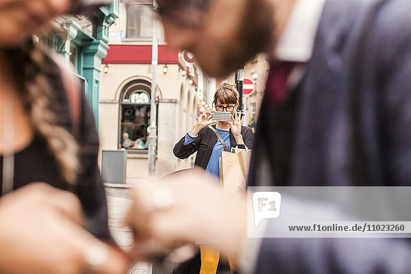 Selective focus of woman photographing friends in foreground through smart phone