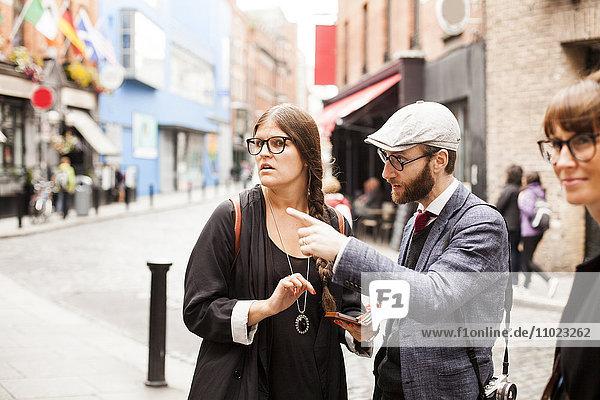 Man talking to female friend on city street