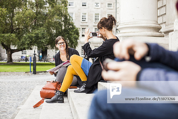 Woman photographing friend while sitting on steps