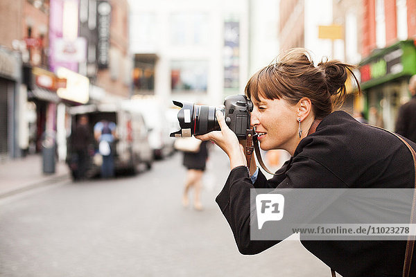 Side view of woman photographing on city street