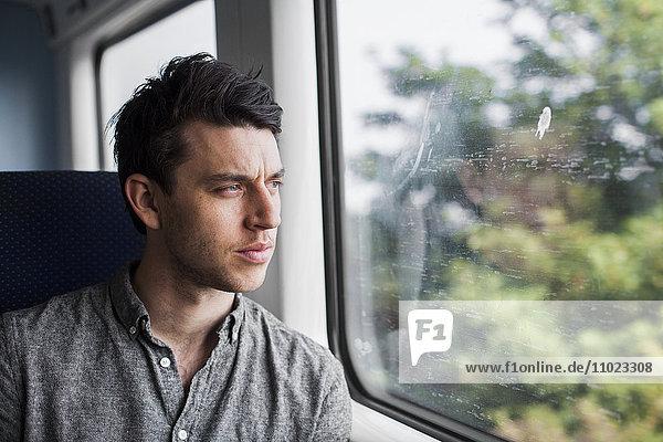 Thoughtful businessman looking through train window