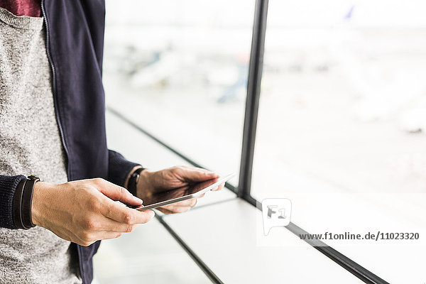 Midsection of businessman using digital tablet by window at airport